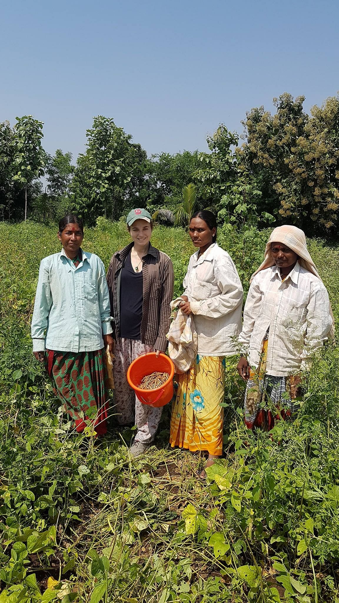 A lady from Europe at the farm with farm attendants, is one of many such who come to learn and help in farming activities