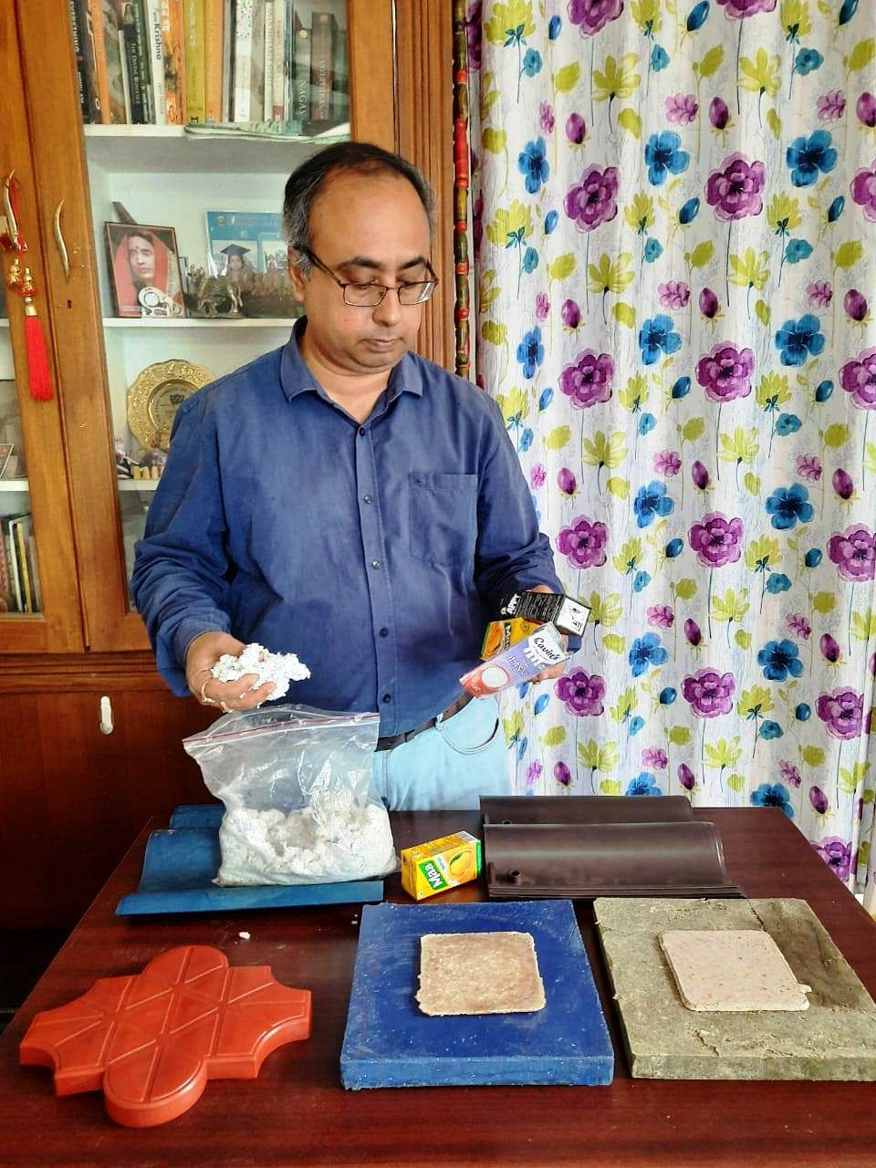 Dr Bhowmik with the roof tiles, paver blocks and upholstery wool all made from waste material