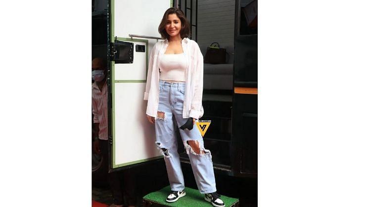 अनुष्का शर्मा पांढऱ्या क्रॉप टॉपवर पांढरा शर्ट परिधान केला आहे. तिने डेनिम जीन्स घातली आहे .