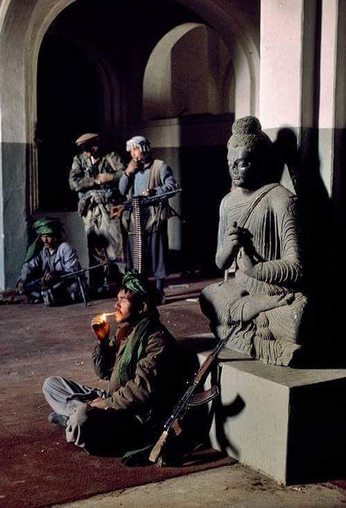 Taliban terrorists surrounding a Buddha statue