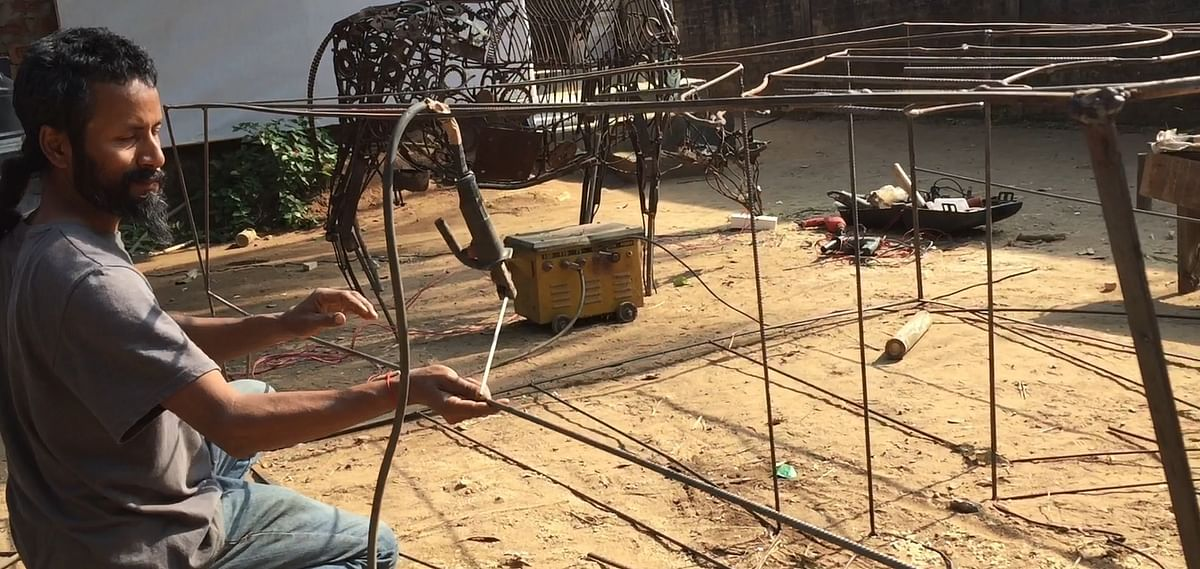 Alak J Pathak, director of festival, working on his metal sculptures