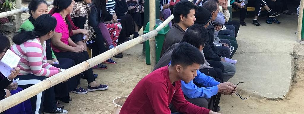 Voters sitting in benches while waiting for their turn at a polling booth in Mizoram during elections last year
