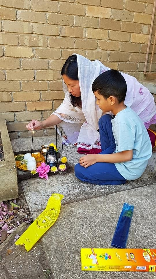 Melbourne resident Surkeinya Nongmaithem showing her son Etash a part of the rituals of Cheiraoba 'puja'