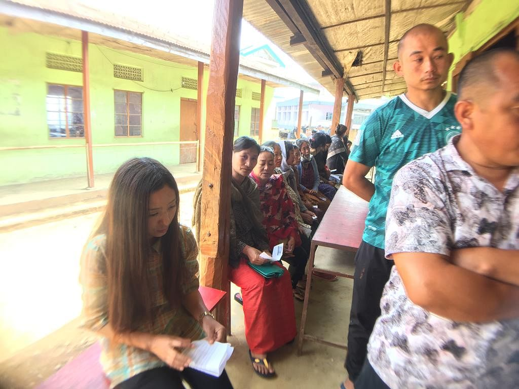 Electors waiting outside a polling station in Nagaland on Thursday. While the men are standing, the women get to sit on benches