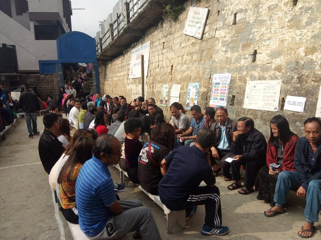 Voters sit on benches provided by the polling booth while waiting in queue during the first phase of Lok Sabha elections in Mizoram on Thursday