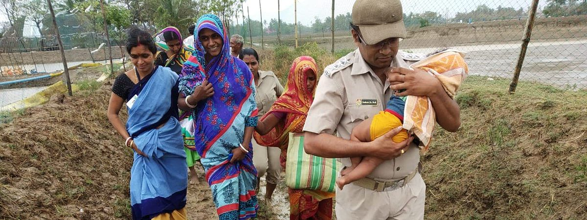 A policeman carrying an infant and guiding children, women, and other locals to safety in Kendrapara, Odisha