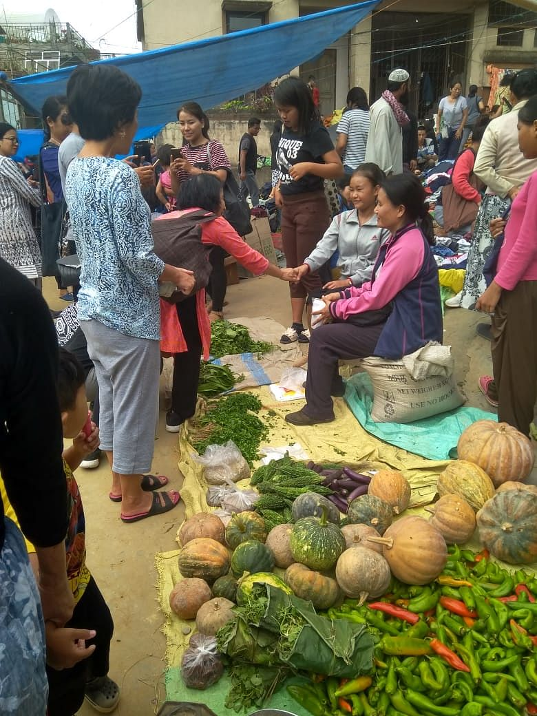 Lalrinnungi being congratulated by a passerby at her vegetable stall in the local market in Aizawl, Mizoram