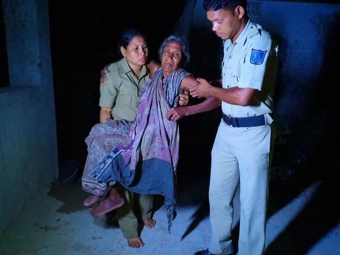Two cops carrying an elderly woman to a designated cyclone shelter in Ganjam