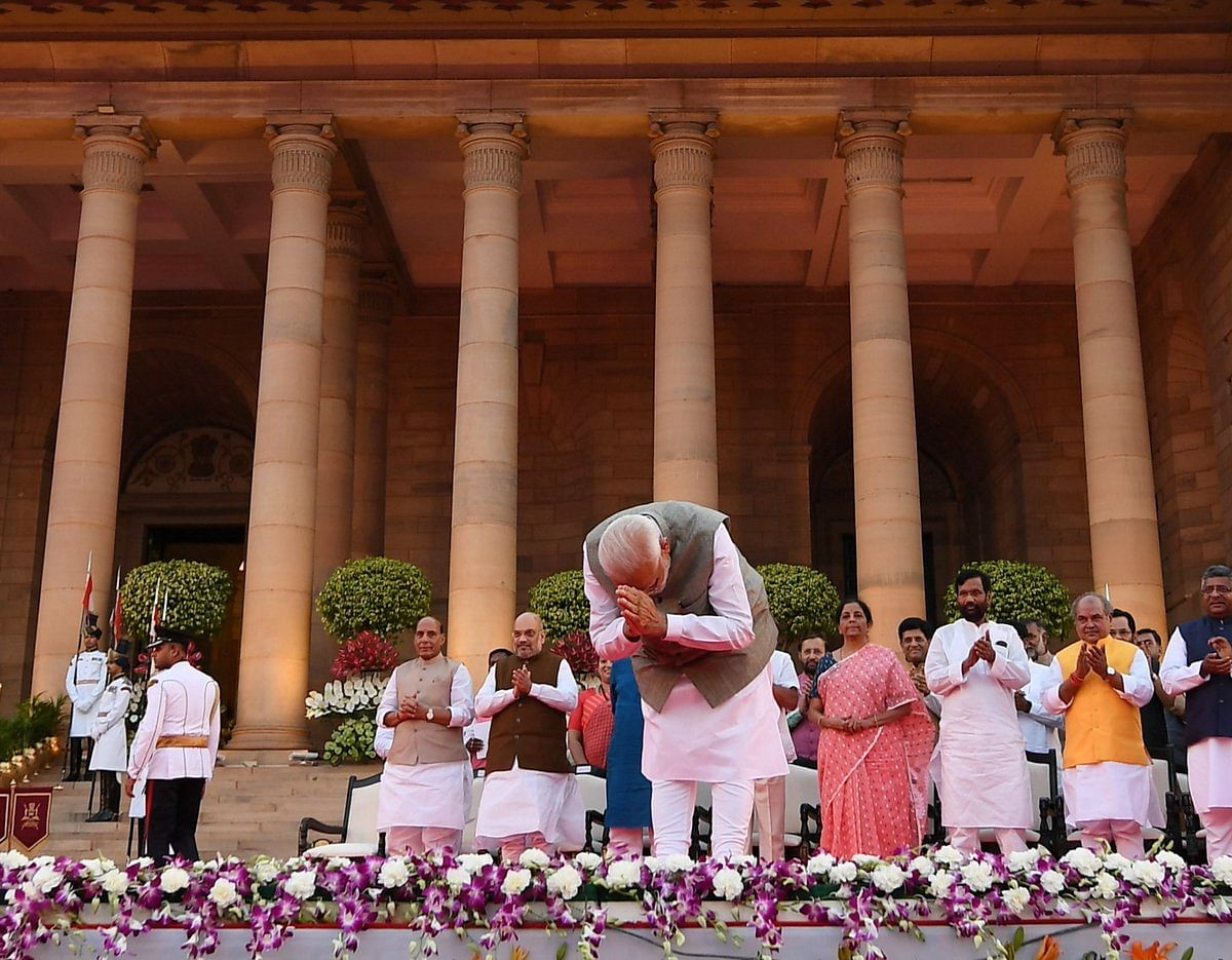 PM Narendra Modi greets the audience ahead of the oath-taking ceremony of his new council of ministers at Rashtrapati Bhavan in New Delhi on Thursday evening