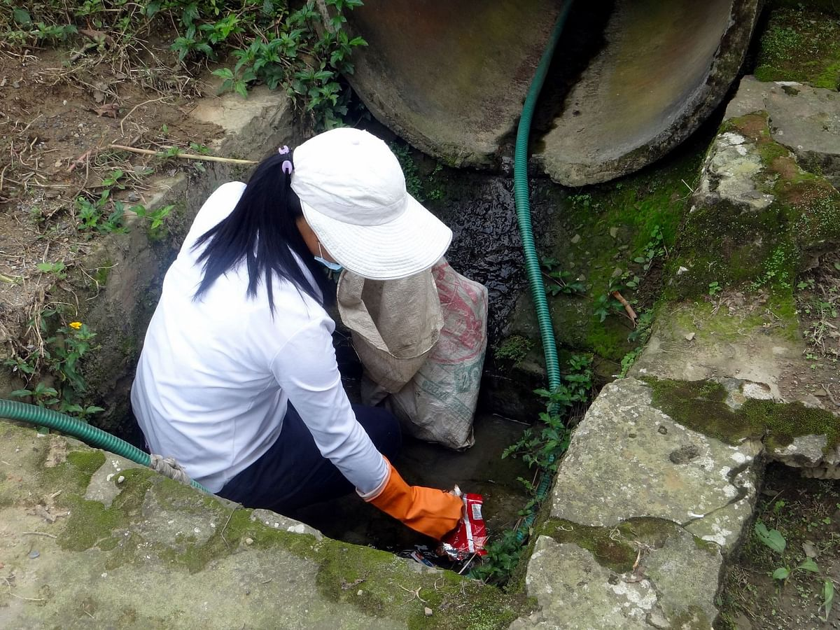 A volunteer cleaning the drains in Mopungchuket village in Nagaland