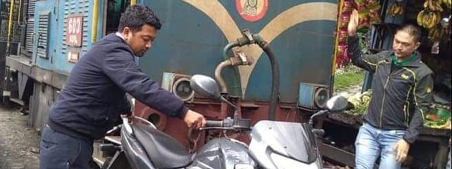 The  image of a driver of a toy train getting down to remove a two-wheeler from the railway tracks in Darjeeling has gone viral on social video