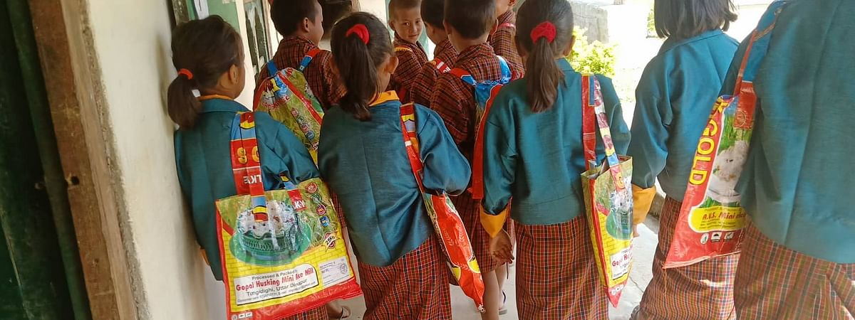 Class II students of Gakidling Primary School in Sarpang dzongkhag of Bhutan carrying school bags made from used plastic rice sacks