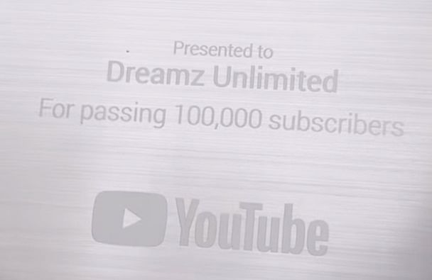 A screenshot of the 'Silver Play Button' with the name 'Dreamz Unlimited' embossed on it