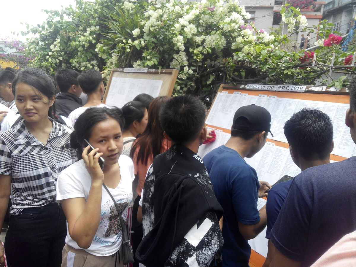 Students checking their results on the notice board in Aizawl, Mizoram on Thursday