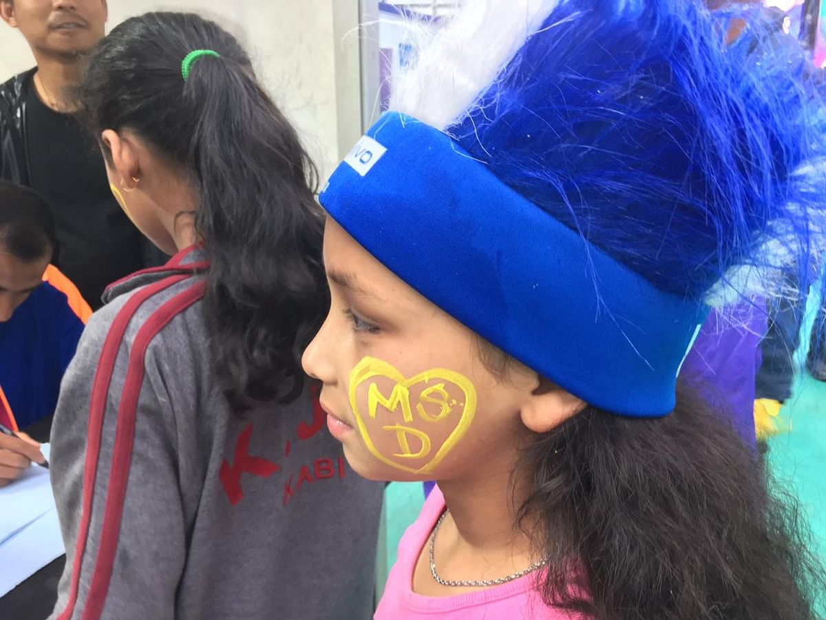 A child gets her face painted at a stall