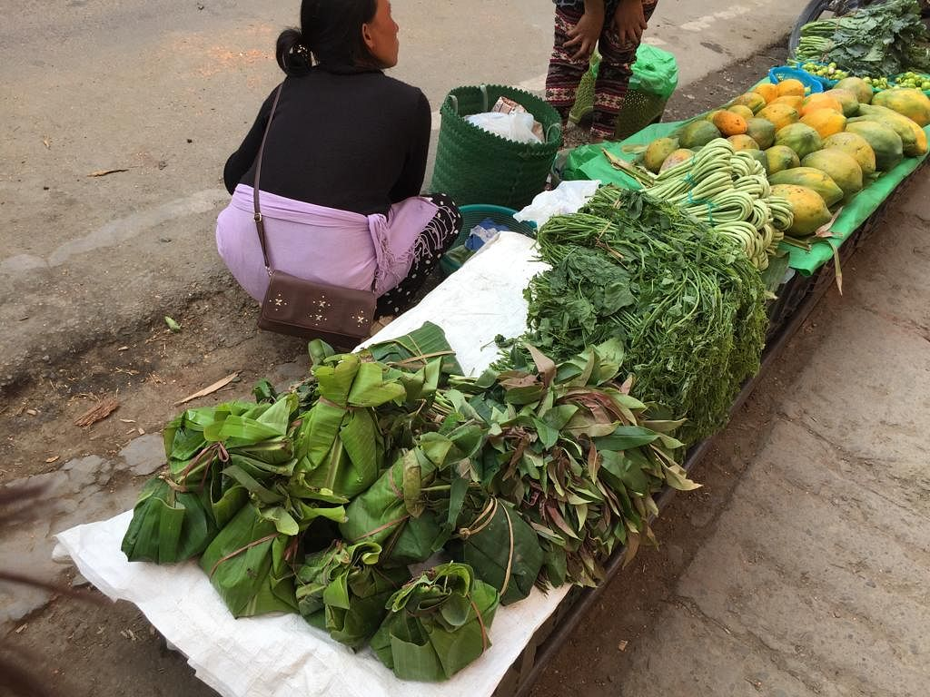 A vendor selling vegetables wrapped in banana leaves at a market in Kohima, Nagaland