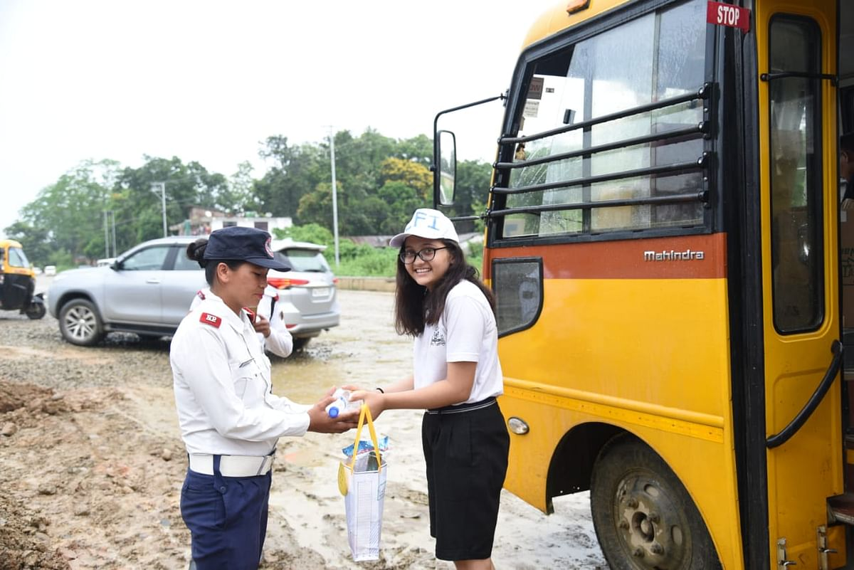 A student of Livingstone Foundation International handing over hampers, snacks to a woman traffic cop on duty in Dimapur, Nagaland
