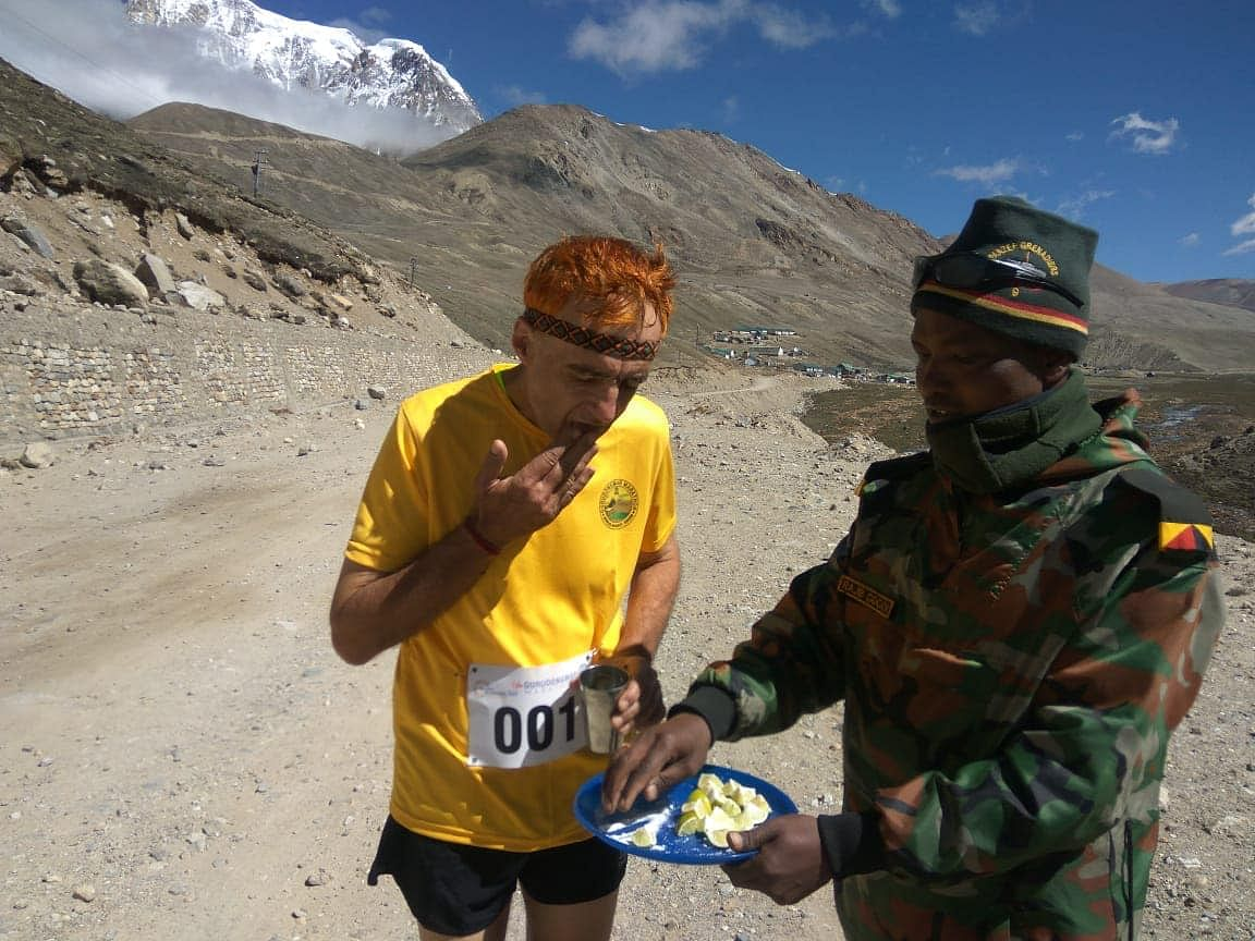 A security man helping a participant of the Gurudongmar Marathon