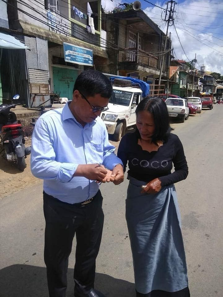 Mizoram MLA ZR Thiamsanga, who is also a qualified doctor, writing a prescription on the palm of patient