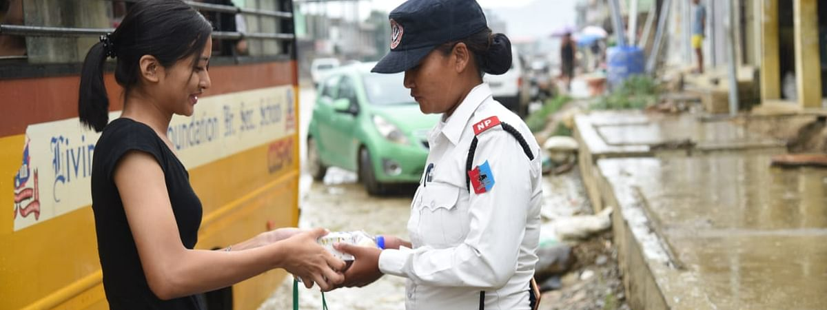 A student of Livingstone Foundation International handing over hampers, snacks to a woman traffic cop in Dimapur, Nagaland