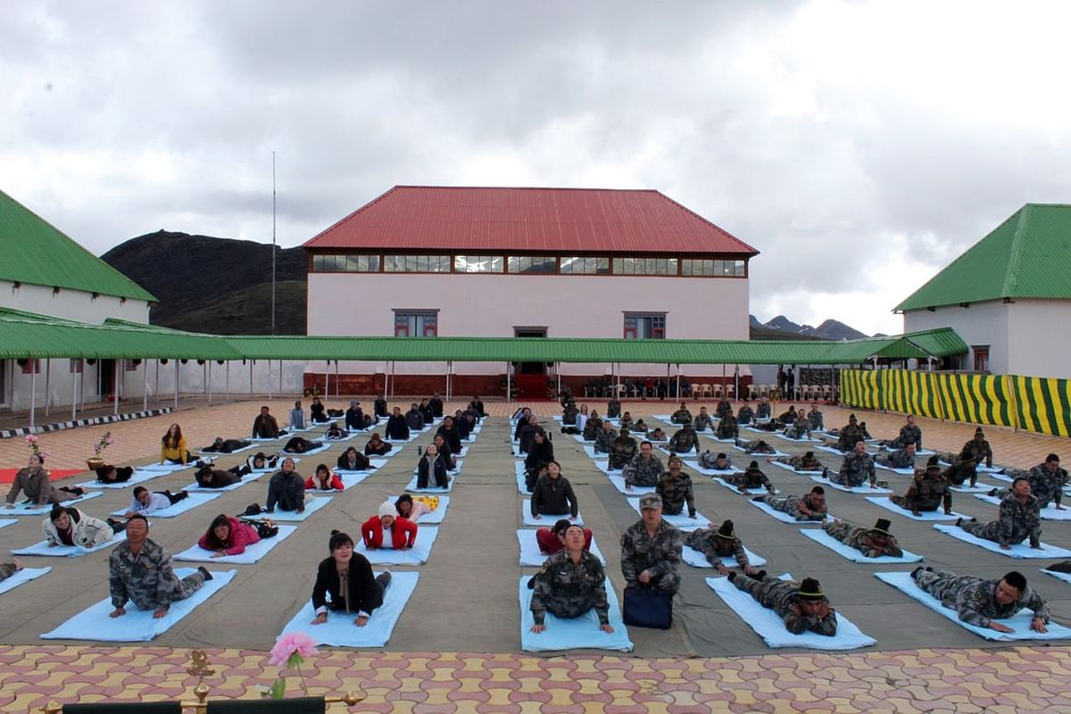 Indian Army and Chinese Army personnel, along with civilians, taking part in a joint yoga session on the occasion of International Yoga Day at Bum La in Arunachal Pradesh on Friday