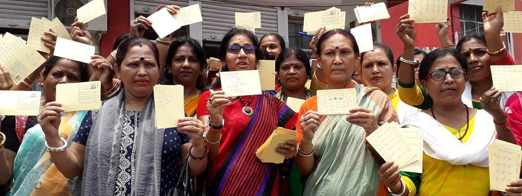Some of the women members of Tripura unit of BJP pose in front of media with the cards writing 'Jai Shri Ram'