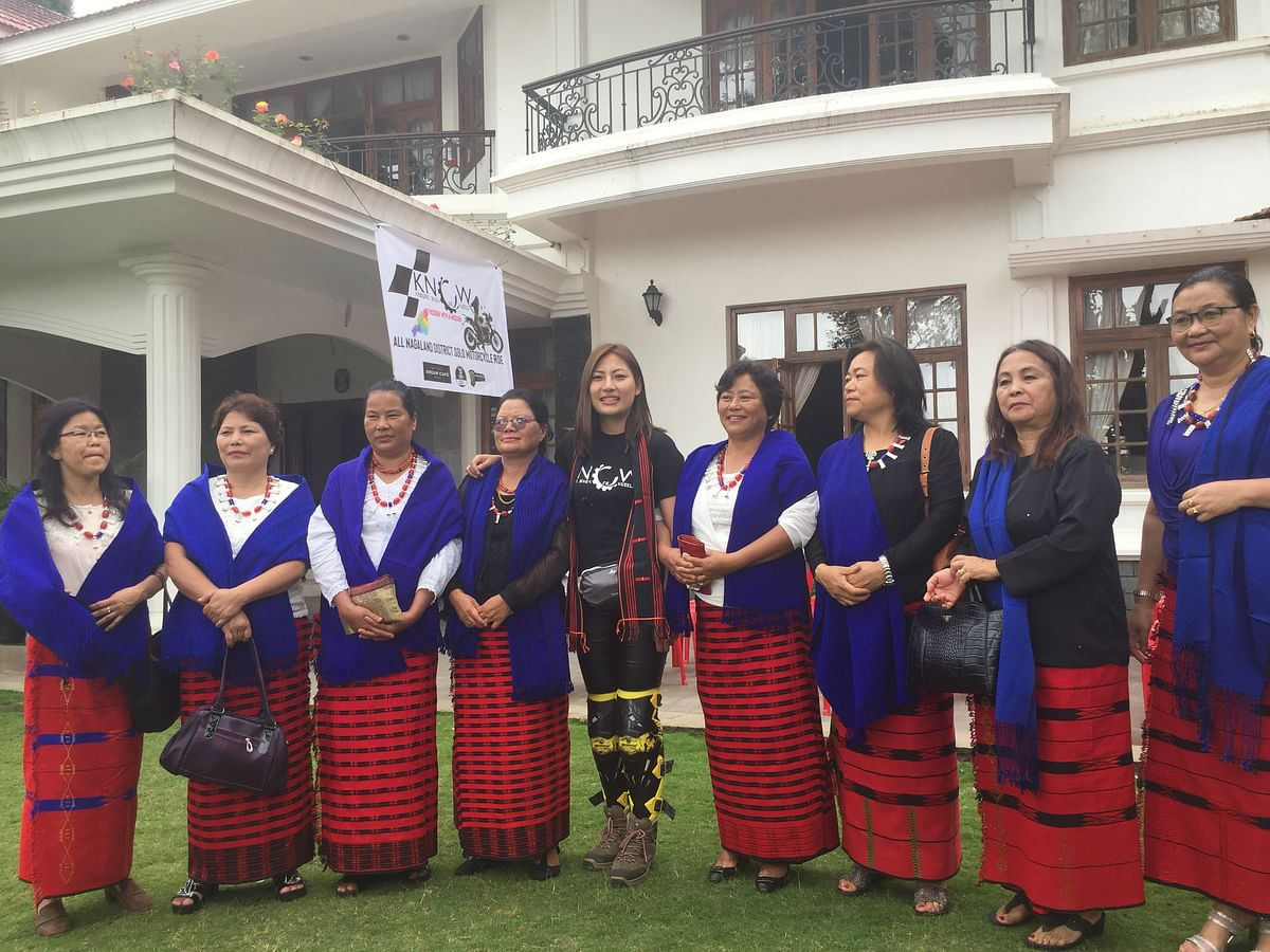 Nagaland biker Onen Nenty with women clad in traditional Ao Naga attire in Kohima on Wednesday