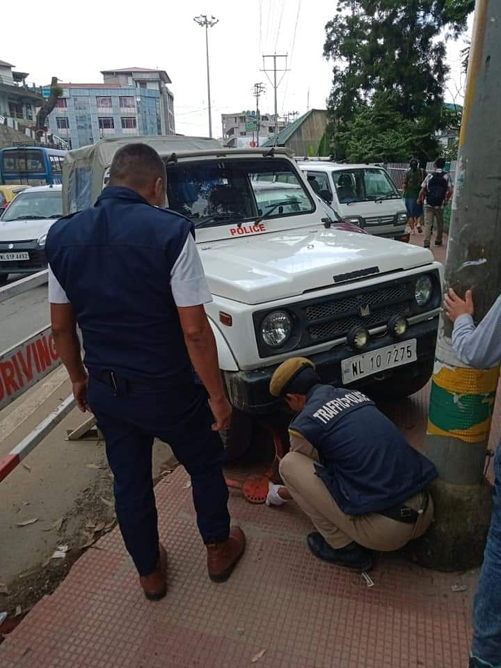Traffic cops clamping the police car parked at a restricted zone over the footpath in Kohima, Nagaland