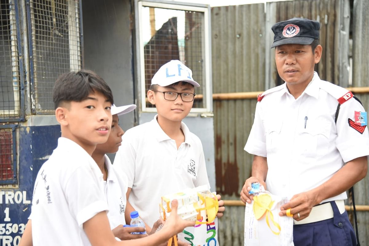 Students of Livingstone Foundation International handing over hampers, snacks to a traffic cop in Dimapur, Nagaland