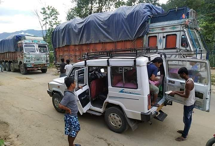 Volunteers from the Sairang Presbyterian Church distributing dal and rice to stranded truck drivers in Mizoram's Aizawl district