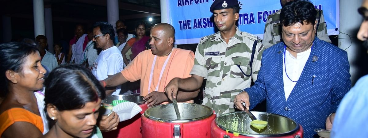 AAI-NER regional executive director Sanjeev Jindal along with members of Akshaya Patra Foundation serving freshly-cooked meals to flood-hit victims of Assam