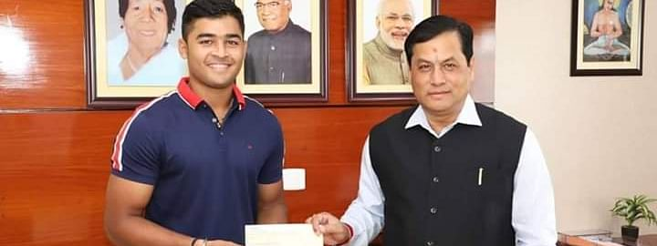 Riyan Parag handing over a cheque of Rs 1 lakh to the Chief Minister's Relief Fund