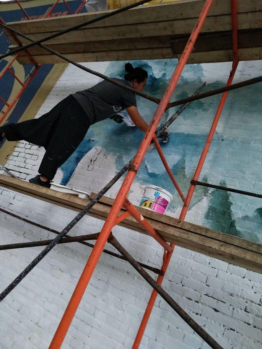 Vineizotuo Tase (30) working on a 60x30 ft wall mural in Vladivostok, Russia