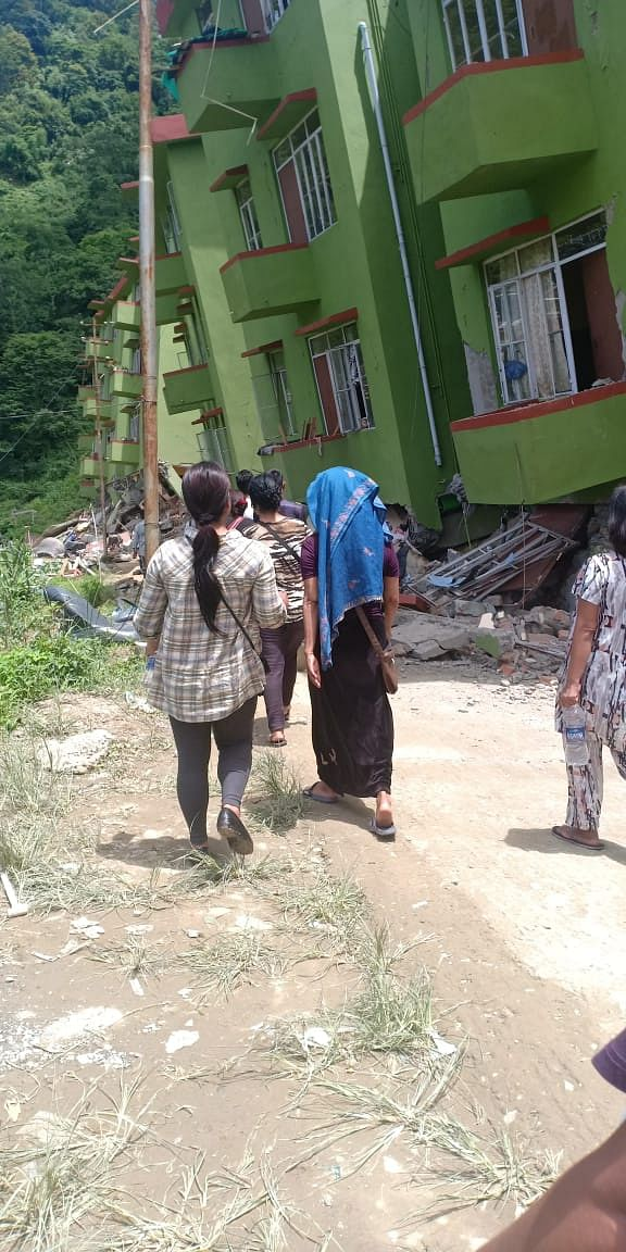 Residents walking through the ruins to collect their belonging