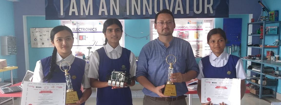 Students of Sikkim's PNG Senior Secondary School along with their coach posing with their championship  trophy at Robotex nationals held in Ahmedabad, Gujarat in July