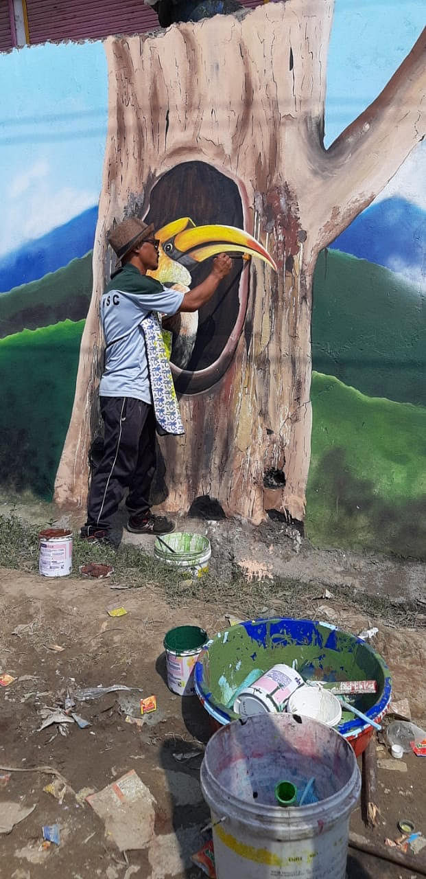 An artist giving final touches to a wall painting in Seppa, East Kameng district, Arunachal Pradesh