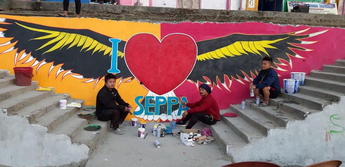 Artists in front of a wall painting in Seppa, East Kameng district