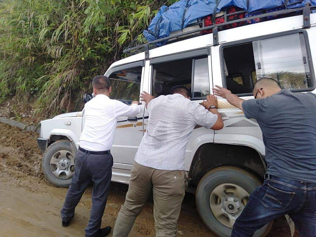 Mizoram Legislative Assembly deputy speaker Lalrinawma (extreme left) helping others to push a stuck vehicle in Lunglei district on Friday
