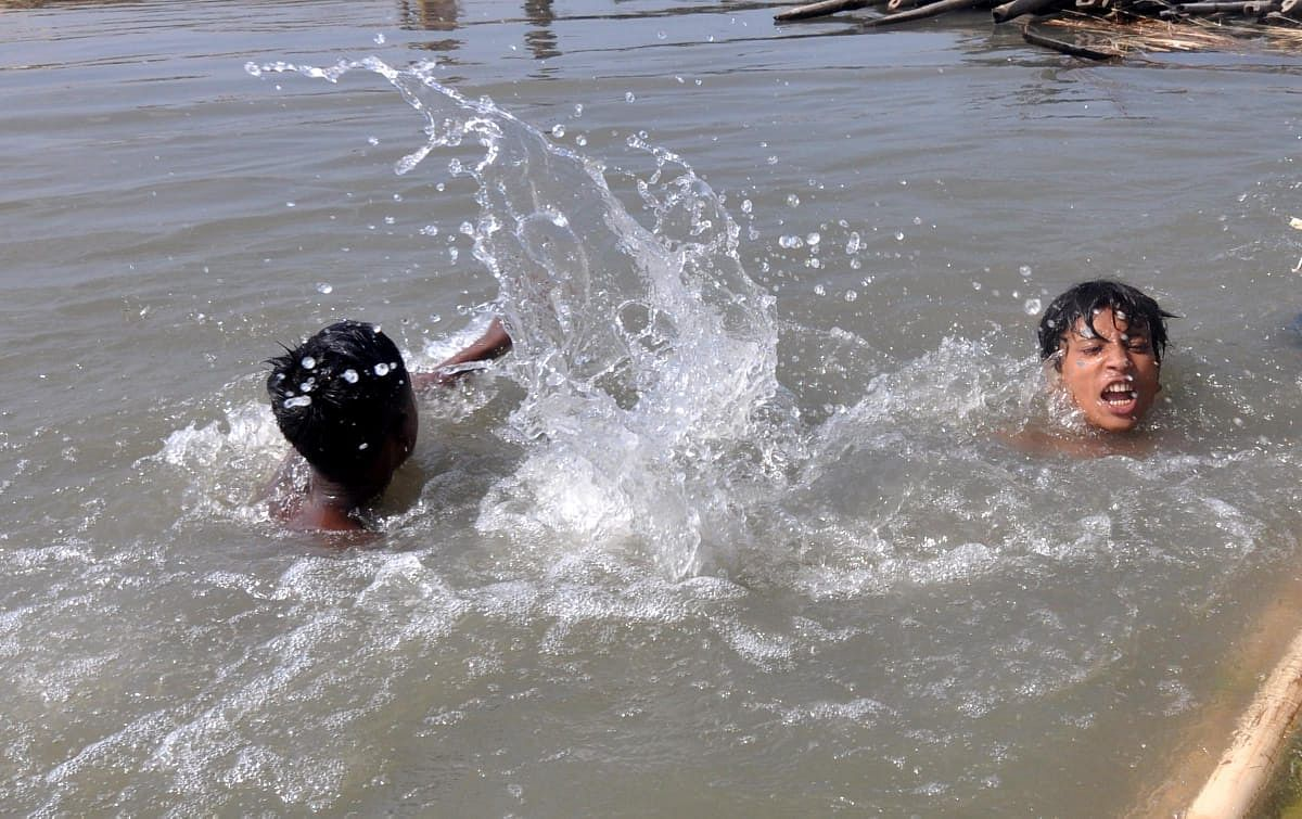 Children trying to beat the scorching heat by swimming in a river