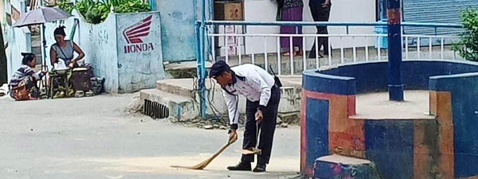 A traffic police sweeping the road near his duty post in Champhai town