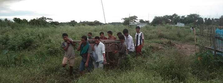 Villagers carrying an ailing man on their shoulders to reach hospital in Karbi Anglong