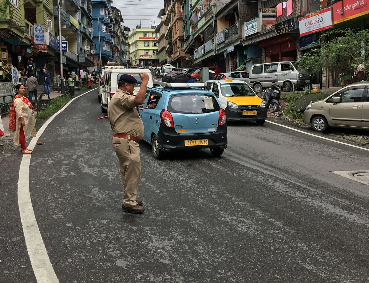 A police official controlling the traffic at Tadong in Gangtok as commuters wait for taxis