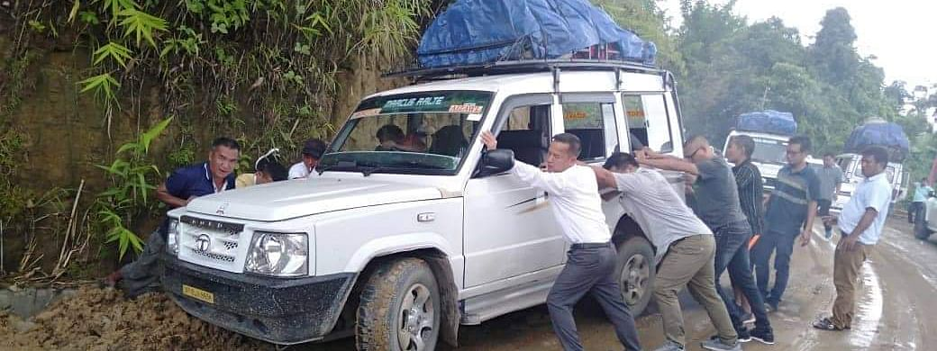 Mizoram Legislative Assembly deputy speaker Lalrinawma getting his hands dirty to join others in pushing the SUV that was stuck in a drain in Lunglei district on Friday