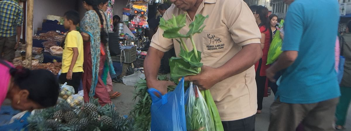 A man using plastic bags while shopping for vegetables in Imphal, Manipur