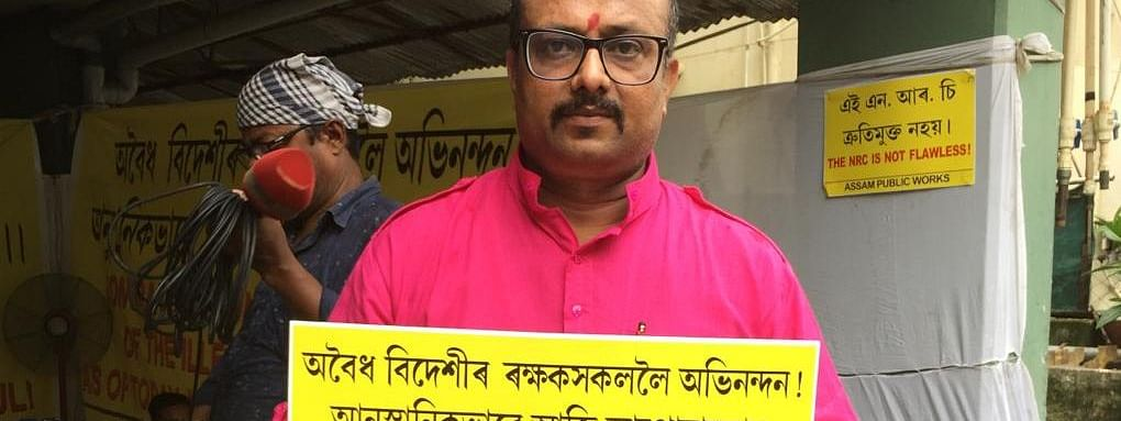 Assam Public Works president Aabhijeet Sarma holding a placard expressing displeasure over the final NRC in Assam