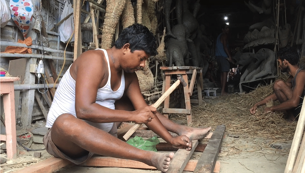 Idol maker Bikram Kumar Paul working on a consignment in Guwahati, Assam