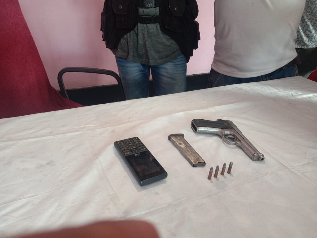 Arms and ammunition, including one pistol, four rounds of live bullets and a mobile handset have been recovered from the arrested DNLA cadre