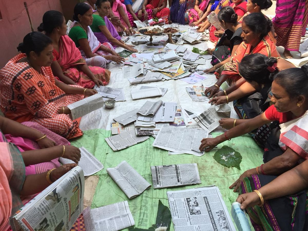 Women in Belona making paper bags out of newspapers