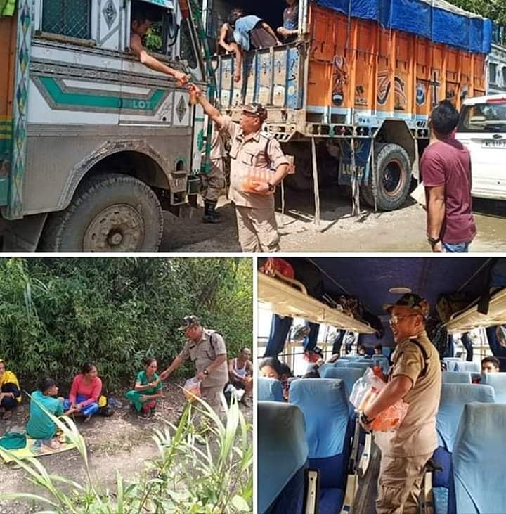 Nagaland police providing juices to travelers stranded due to landslides in Zubza on Thursday