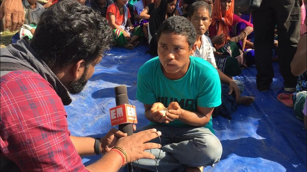 A Bru members interacts with EastMojo while having puffed rice donated by local villagers